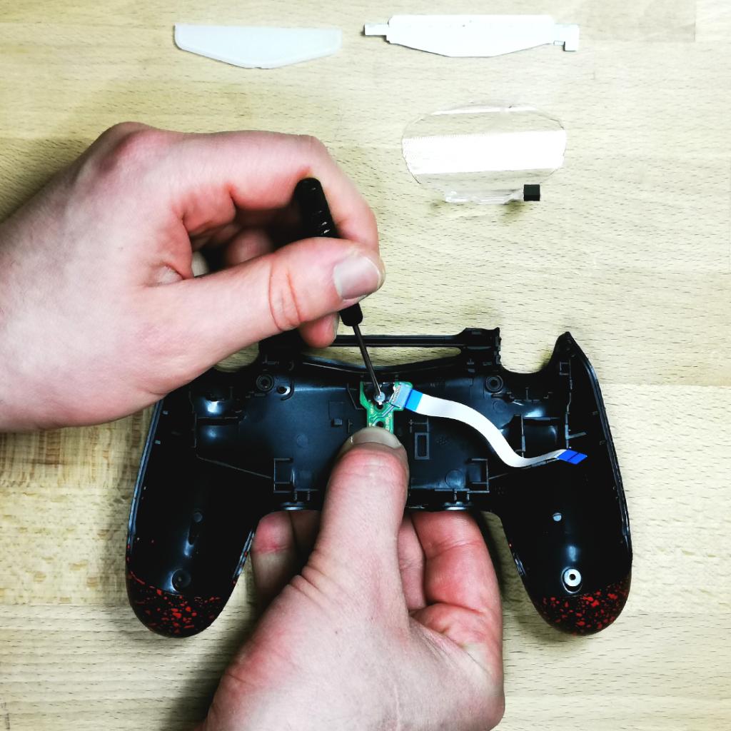 D2montage manette PS4 pour la personnalisation.  Dévissez la carte mère ainsi que la fiche de la coque arrière